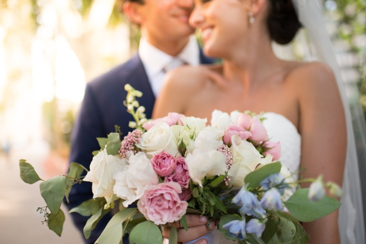 Close up of wedding flower bouquet with bride and groom in background