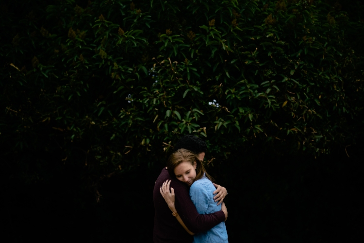 Engagement shoot hugging by a tree