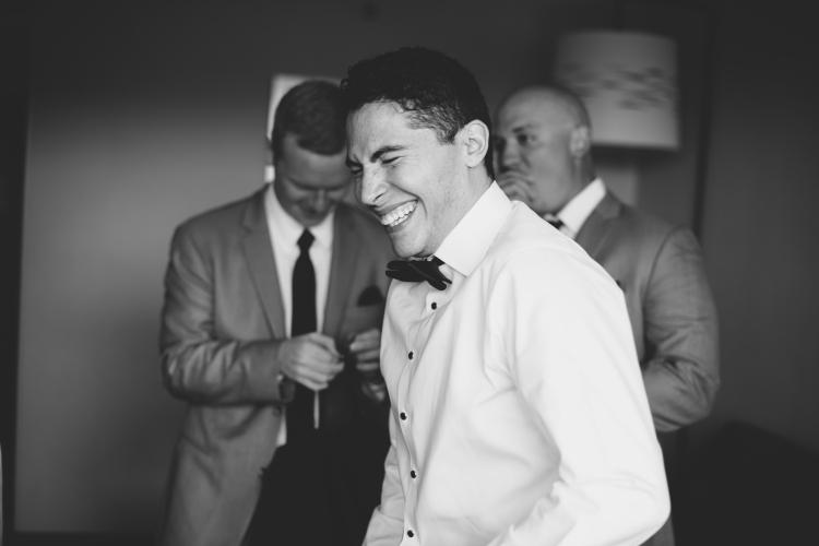 Groom laughing with groomsmen on wedding day