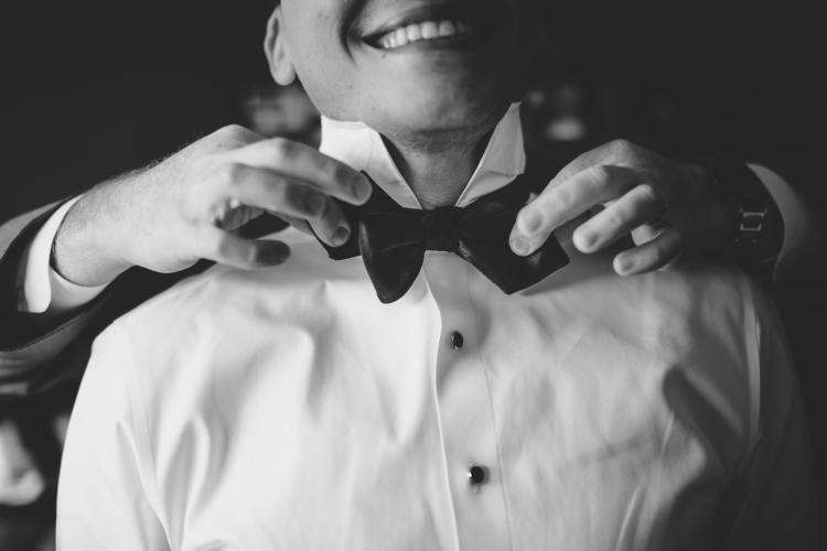 Groom getting ready, putting on bow tie