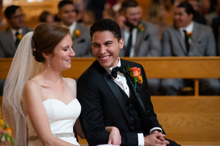 Bride and groom sitting laughing during their wedding